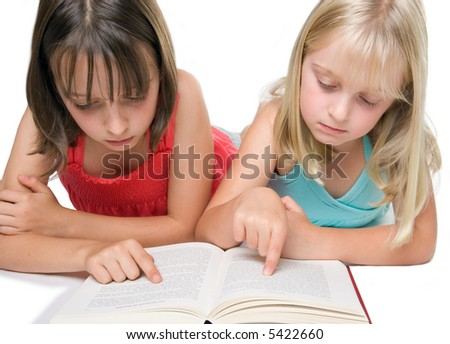 Two young sisters reading a book