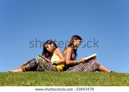 two young sisters reading books at the park