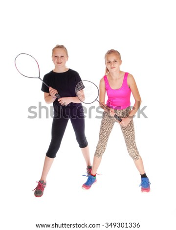 Two young sisters standing isolated for white background with there tennis racket in there hands  - stock photo