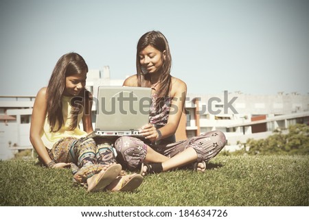 two young sisters using the internet at the park on her laptop