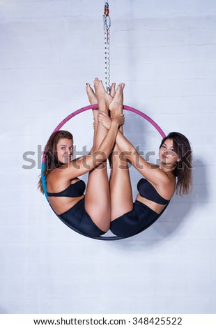 Two young slim sports women on ring in bright white interior - stock photo