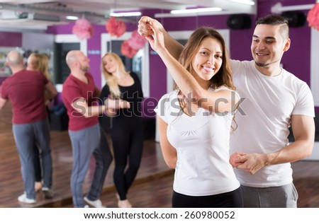 Two young smiling couples having dancing class in club - stock photo