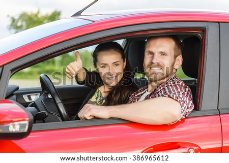 Two young smiling people in a red car. Girl showing thumbs up. Concept of travel, rent car or buying car.  - stock photo