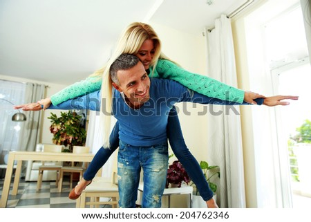 Two young smiling person with the hands lifted upwards at home - stock photo