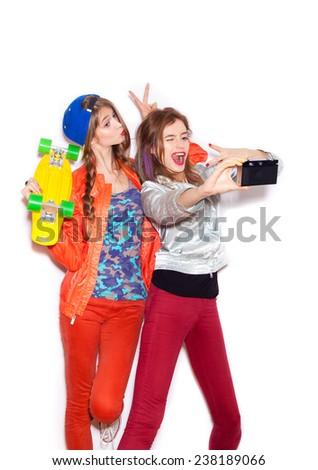 Two young sporty girls have fun together.  Beautiful women making selfie. Emotion.  Hairstyle. Makeup.  White background, not isolated - stock photo