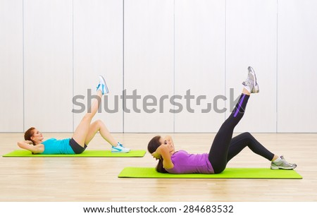 Two young sporty women at fitness club - stock photo