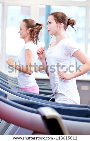 Two young sporty women run on machine in the gym centre
