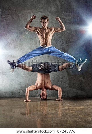 Two young strong men dancing. - stock photo