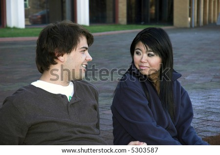 Two young students chatting on steps outside their college. - stock photo