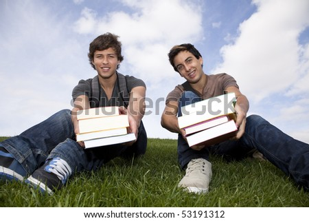 two young students giving you books - stock photo