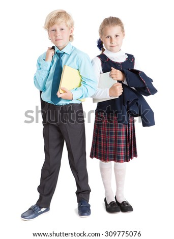 Two young students in uniform standing full-length with books in hands, isolated on white background
