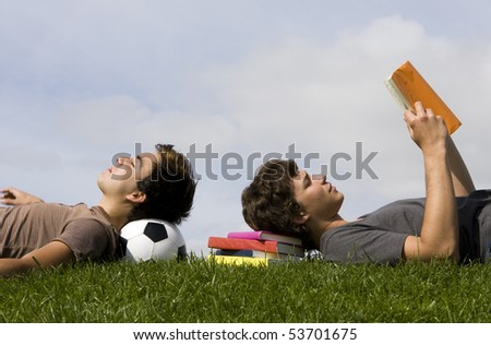 Two young students lying on the grass - stock photo