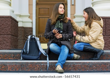Two young students on the stairs of a high school. - stock photo