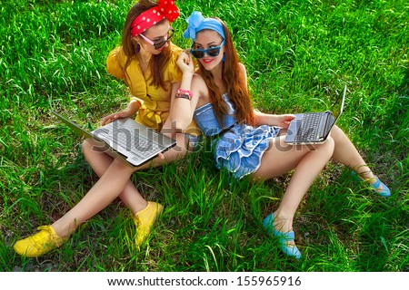 Two young stylish woman using laptops back to back  on a green lawn - stock photo