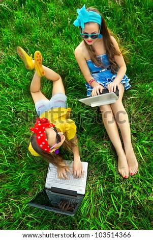 Two young stylish woman using laptops lying on a green lawn - stock photo