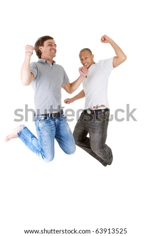 Two young successfull jumping in joy! Two handsome multiracial models. - stock photo