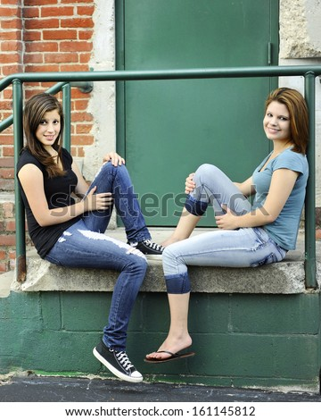 Two young teen girls relaxing together on an old warehouse stoop.  - stock photo