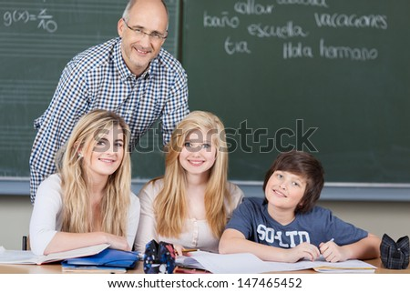 Two young teenage female students and a younger boy in class with their attractive male teacher standing behind them in front of the chalkboard - stock photo