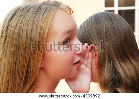 Two young teenage girls gossiping in school yard - stock photo