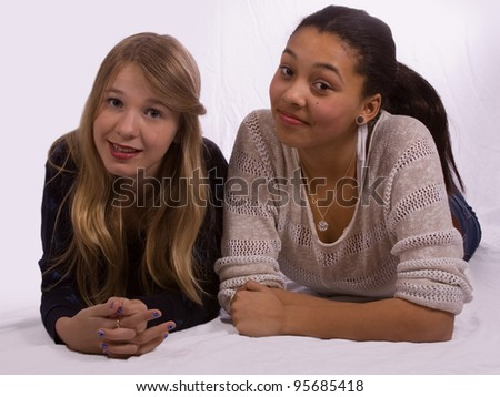Two young teenage girls posing one mixed race and one blond caucasian - stock photo