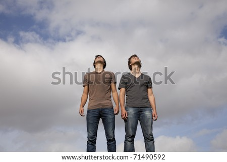 two young teenager enjoying the fresh air looking up - stock photo