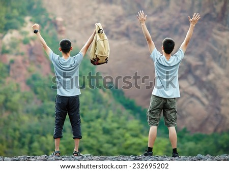 Two young tourist men standing with raised hands on rocky cliff - stock photo