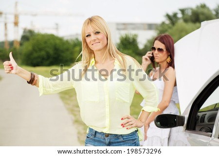 Two Young tourist women Hitchhiking on the road and waiting for help because of Car troubles.