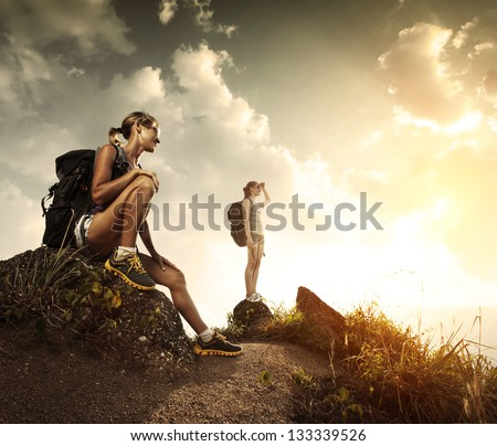 Two young tourists with backpacks relaxing on rocks and enjoying sunset - stock photo