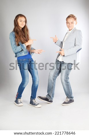 Two young trendy teenagers posing in studio, making faces. - stock photo