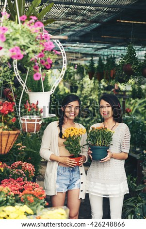 Two young Vietnamese women holding pots with beautiful bright flowers - stock photo