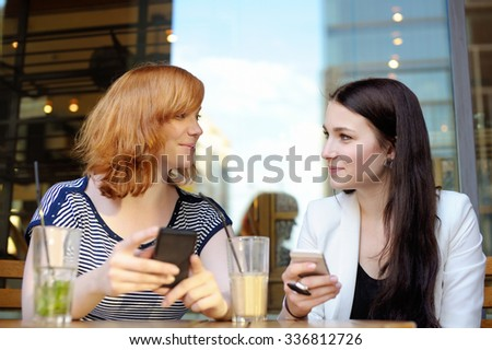 Two young woman at the outdoors cafe - stock photo