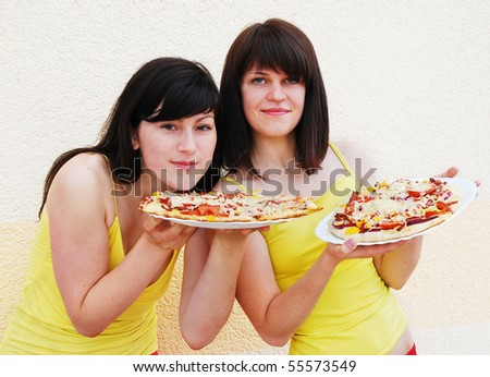 Two young woman eating