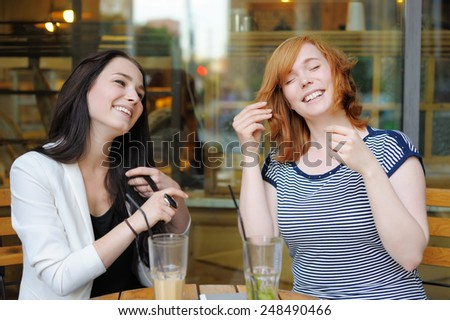 Two young woman having fun at the outdoors cafe  - stock photo