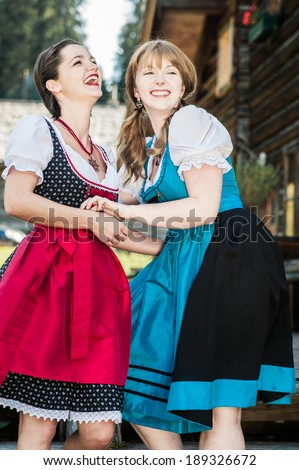 Two young Woman in traditional austrian Clothes having Fun
