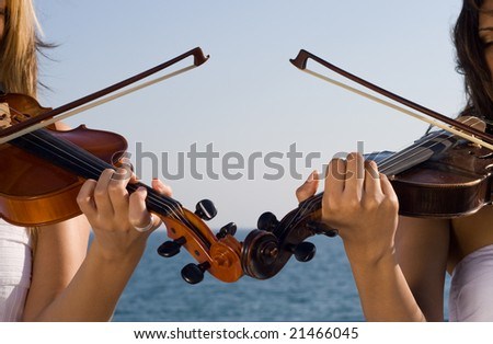 two young woman play violin on beach - stock photo