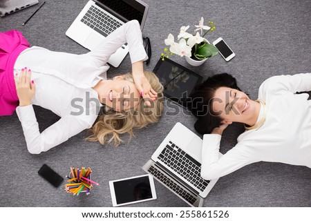 Two young woman relaxing in the office, view from above