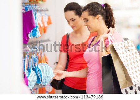 two young woman shopping for lingerie in clothing store - stock photo