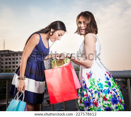 Two young woman shopping. Outdoors shot - stock photo