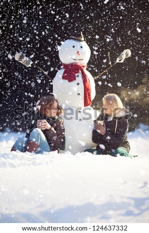 Two young woman sitting near snowman and drinking hot tea while it's snowing
