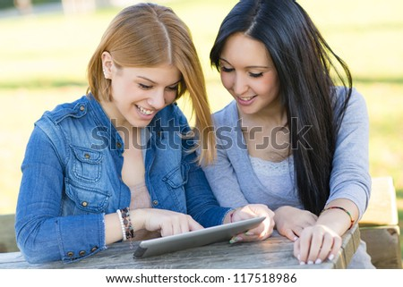 Two young woman smiling using a tablet - stock photo