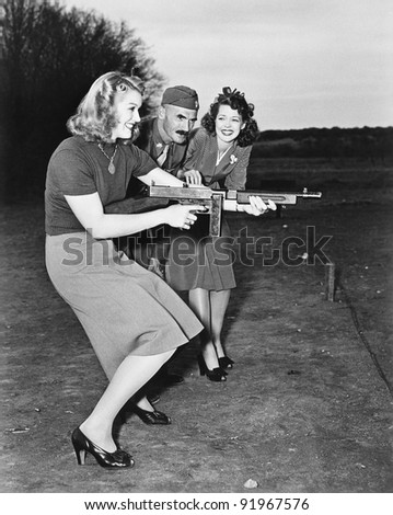 Two young women and a soldier trying out a machine gun - stock photo