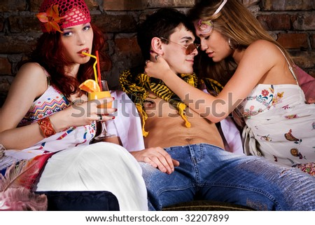 two young women and man on a party, indoor shot - stock photo