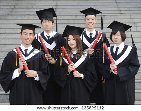 Two young women and three man celebrating their graduation