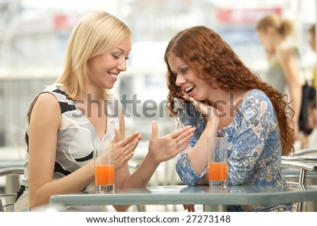 Two young women are cheered in a cafe - stock photo