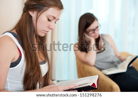 Two young women are sitting and reading books. - stock photo