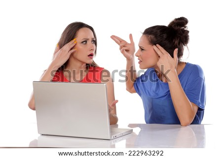 Two young women arguing behind the laptop  - stock photo