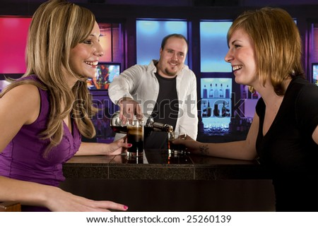 two young women at the bar having drinks - stock photo