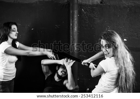Two young women beating and shooting man on black-and-white background - stock photo