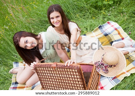Two young women - best friends sitting on a blanket and having fun at a picnic. - stock photo