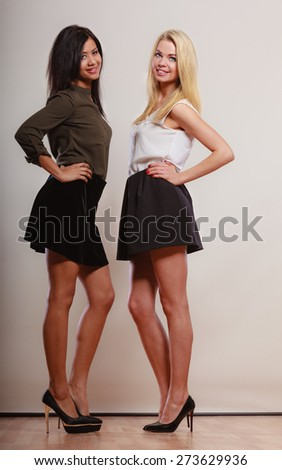 Two young women caucasian and african in trendy short black skirts posing in full length studio portrait on gray
